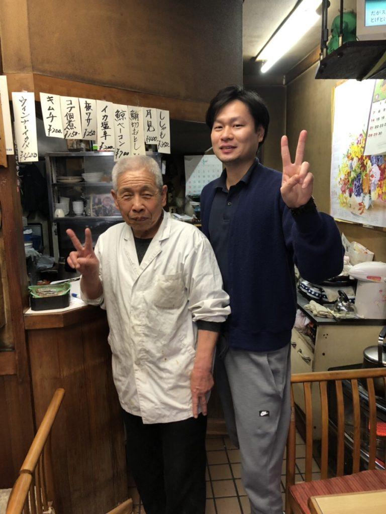 ライムパーソナルジムのパーソナルトレーナー阿久津さんが定食屋さんの店主とピースをしている