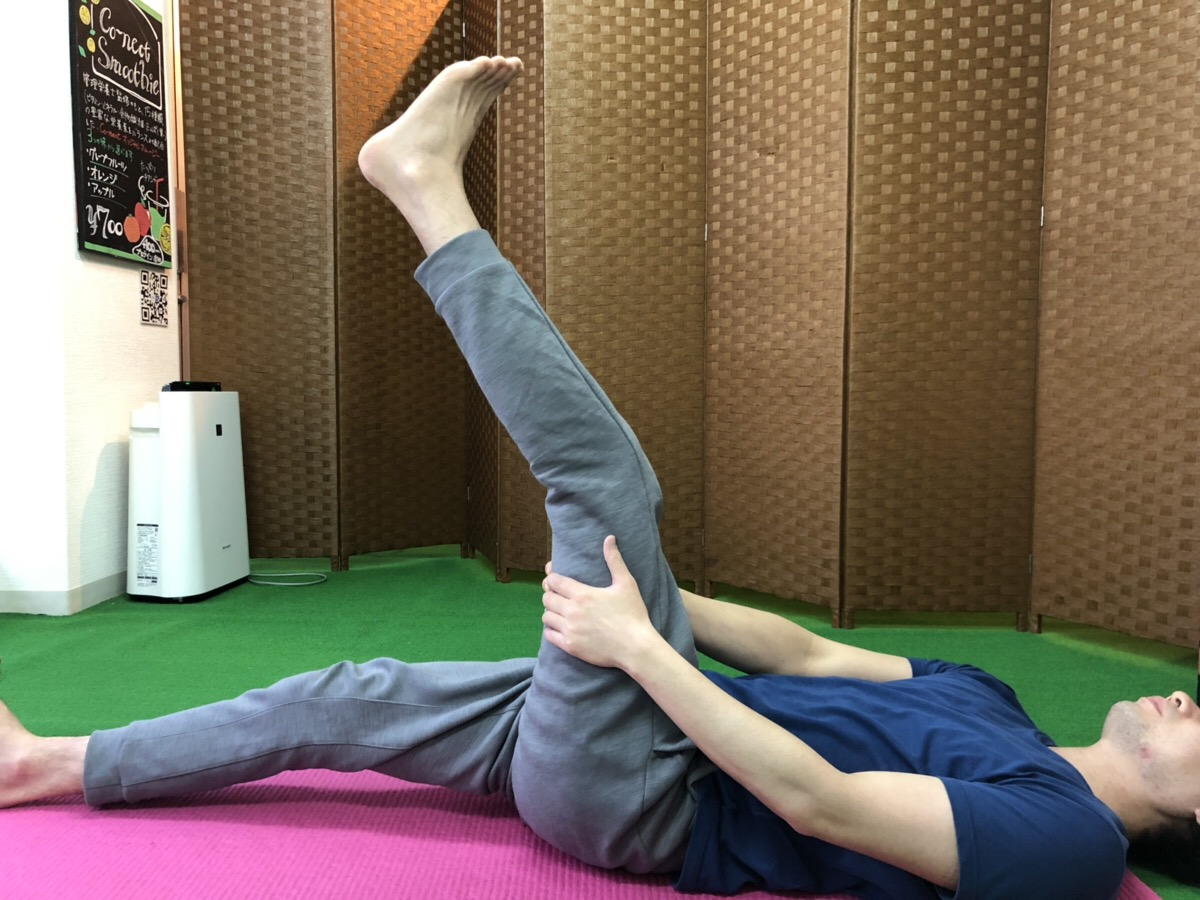寝転がって足を上げてももの裏を伸ばすストレッチをしているところ